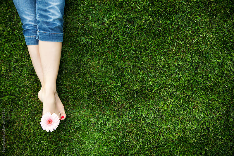 Grass: Anonymous Woman Lying on Grass with Flower in Toes by Sean Locke for Stocksy United