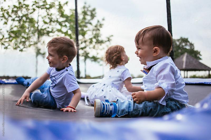 Kids playing at trampoline by Marko Milovanović for Stocksy United