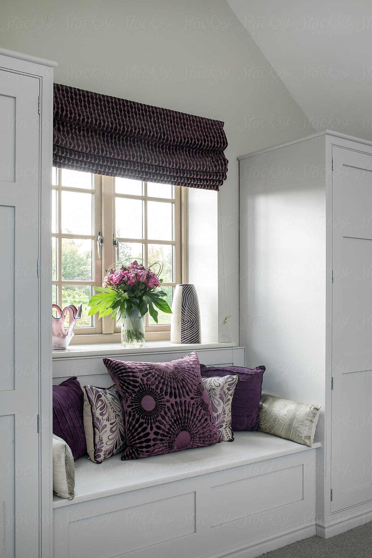 Integrated bedroom storage units around a window with matching