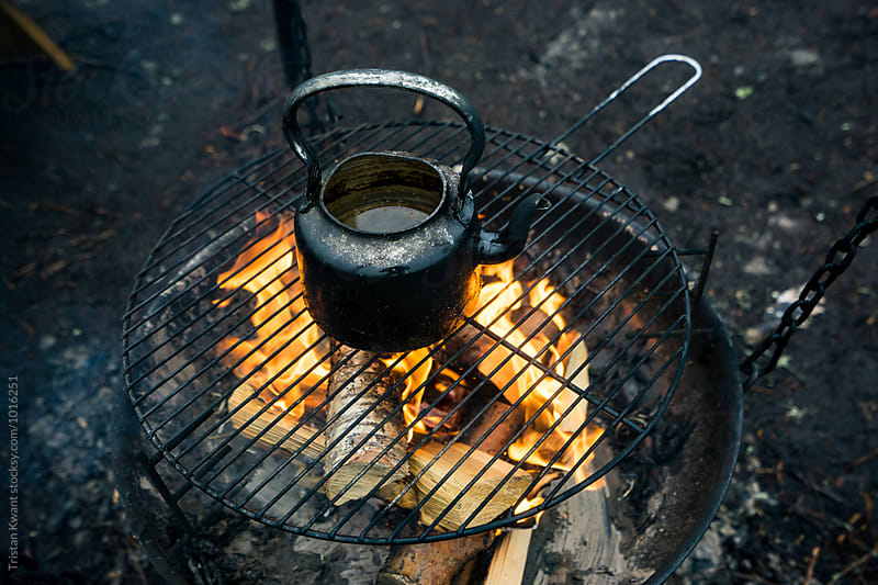 Boiling water for thee in a kettle on the campfire by Tristan Kwant for Stocksy United