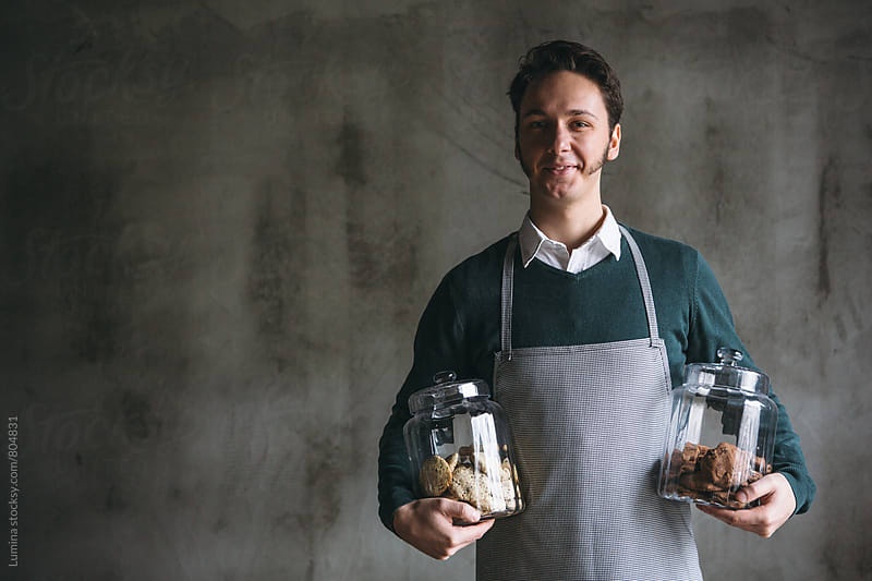 Man in an Apron Hollding Jar Full of Cookies by Lumina for Stocksy United