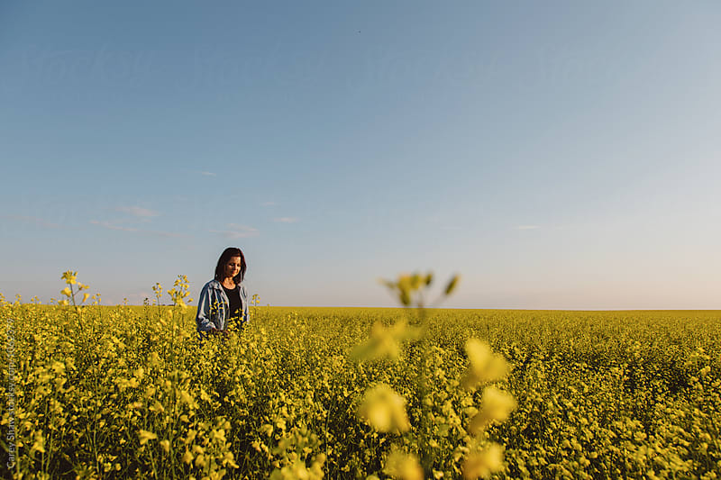Female farmer standing in field of canola by Carey Shaw for Stocksy United