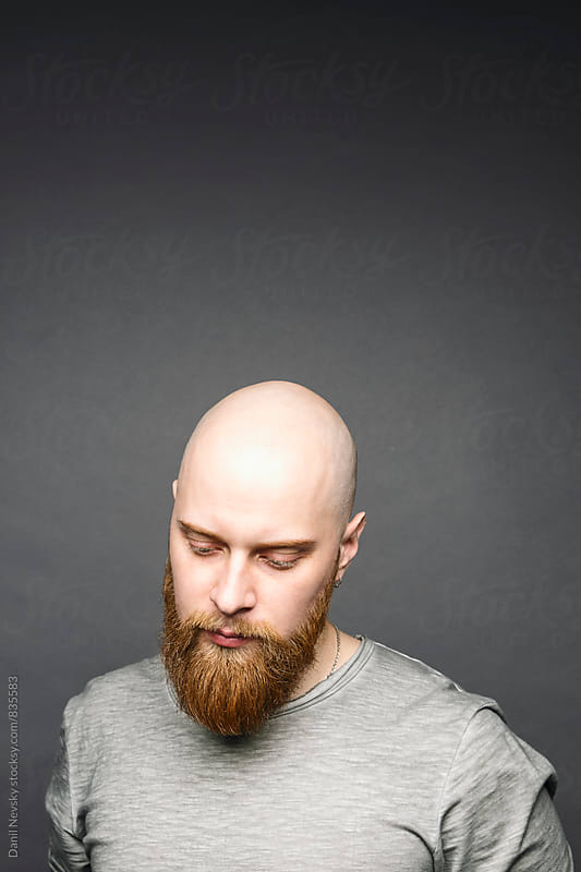 Portrait of bald man with red beard looking down by Danil Nevsky for Stocksy United