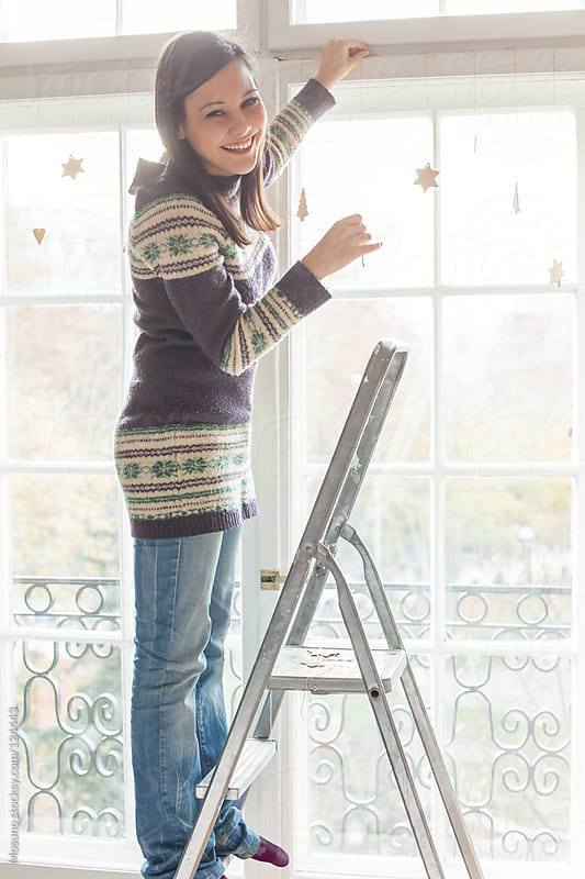 Woman Standing on Ladder and Decorating a Window by Mosuno for Stocksy United