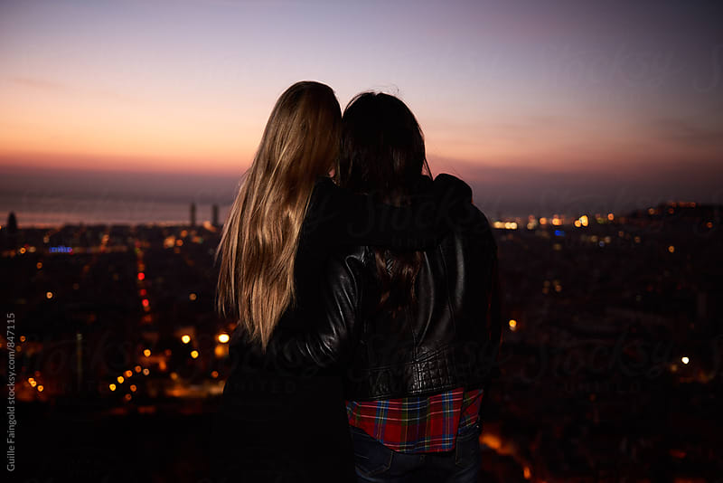 Two girlfriends hugging while looking at evening cityscape by Guille Faingold for Stocksy United