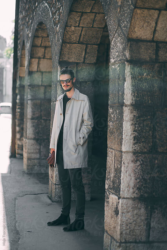 Young fashionable man walking on the street by Maja Topcagic for Stocksy United