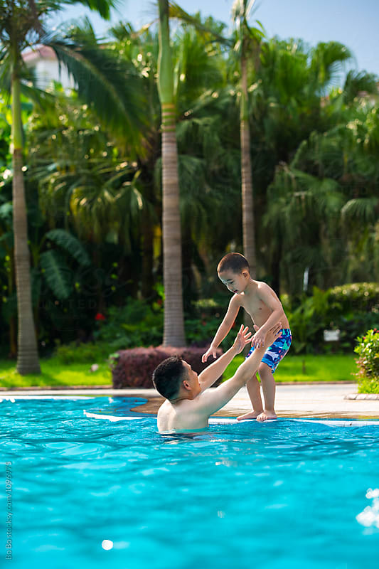 son and father in the outdoor swimming pool by Bo Bo for Stocksy United