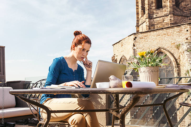 Beautiful redhead businesswoman working with laptop on a outdoors home office. by BONNINSTUDIO for Stocksy United