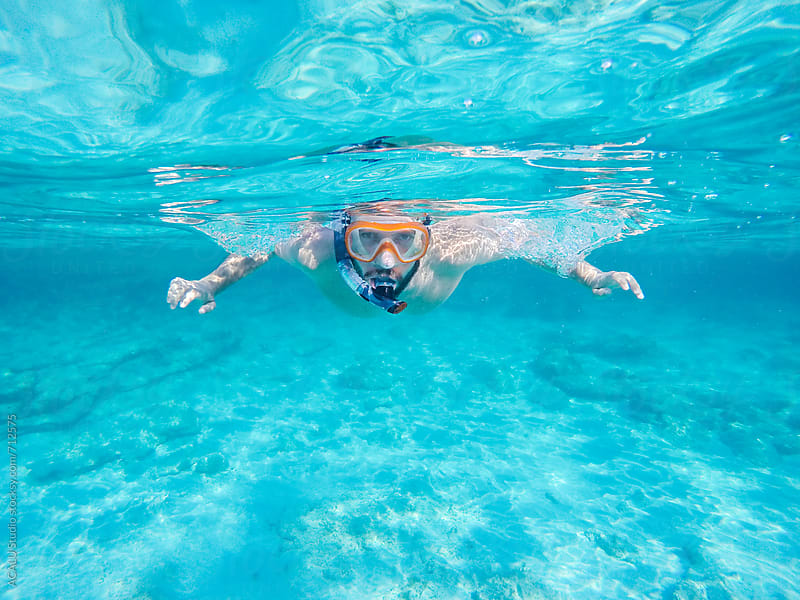 Young man snorkeling by ACALU Studio for Stocksy United