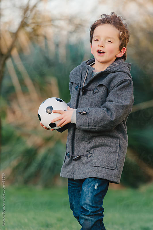 Child ready to throw soccer ball by Rebecca Spencer for Stocksy United