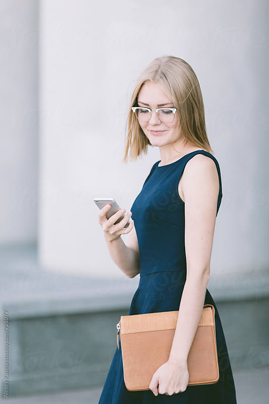 Young businesswoman  with smartphone on the street.  by Alexey Kuzma for Stocksy United