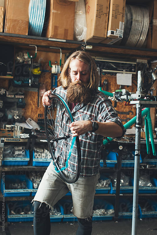 Long-Haired Hipster Mechanic Assembling Wheel of Fixed Gear Bike in Bright Workshop by VISUALSPECTRUM for Stocksy United