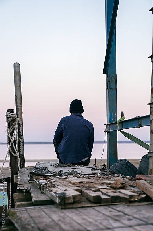 Lonely fisherman sitting on wooden pier and looking seaward by Danil Nevsky for Stocksy United