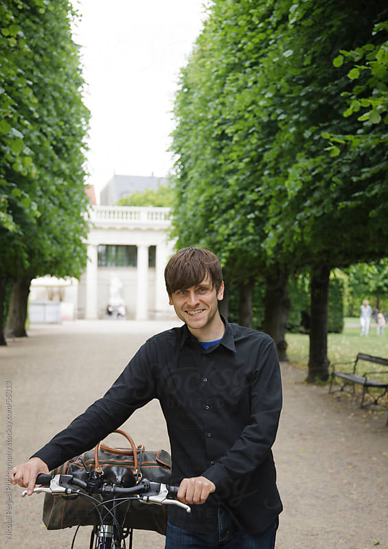 Man with a bike cycle in a park by Nicolai Perjesi Photography for Stocksy United