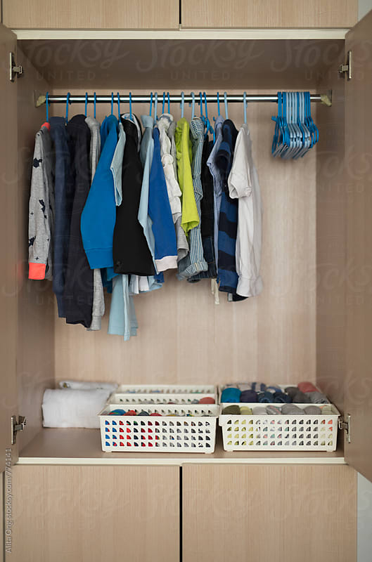 Neatly organised kid's wardrobe after decluttering by Alita Ong for Stocksy United