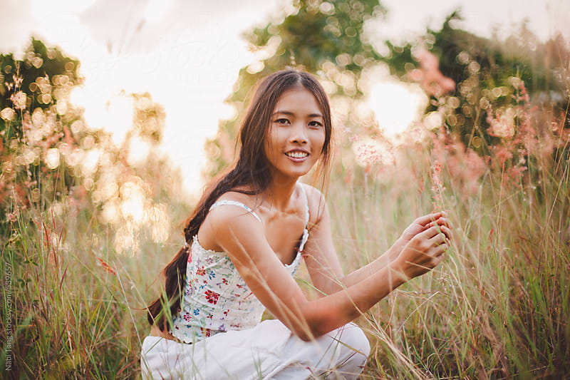 Beautiful young woman in the long grass field on the mountain by Nabi Tang for Stocksy United