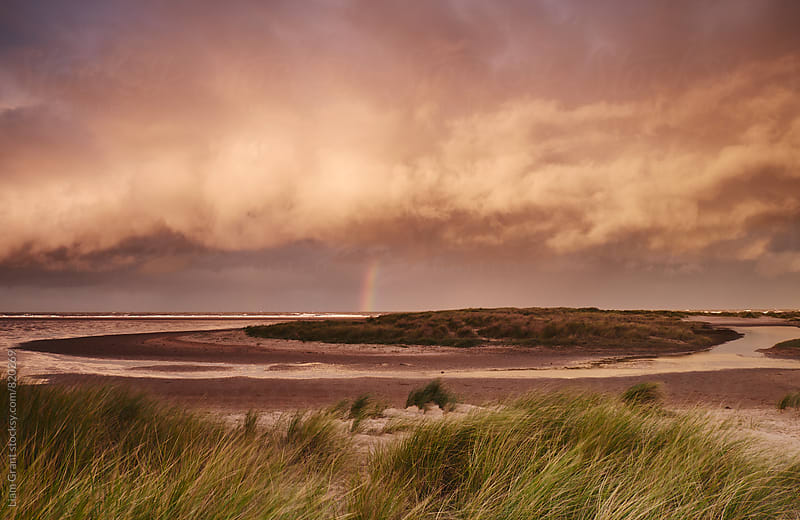 Storm clouds and rainbow at sunset. Holkham, Norfolk, UK. by Liam Grant for Stocksy United