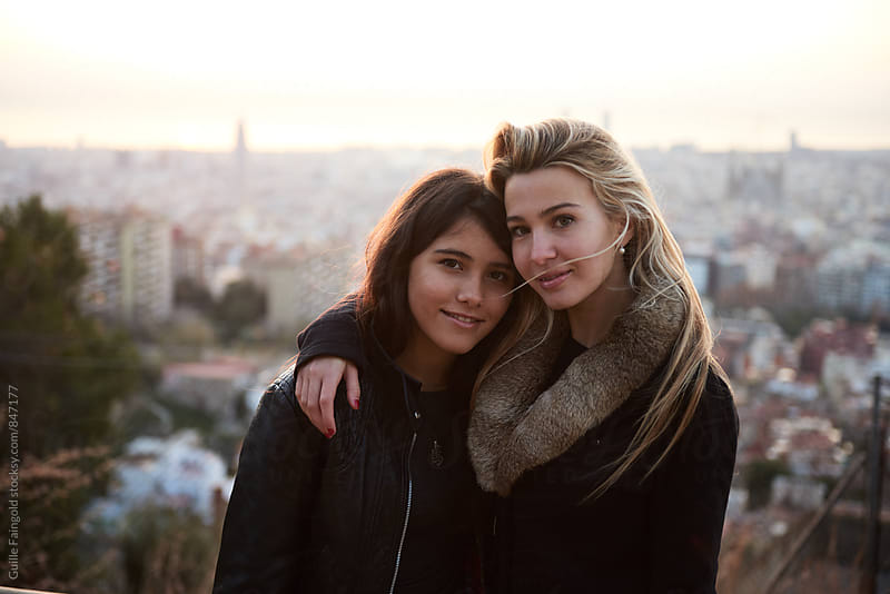 Two beautiful young women looking at camera against of cityscape by Guille Faingold for Stocksy United