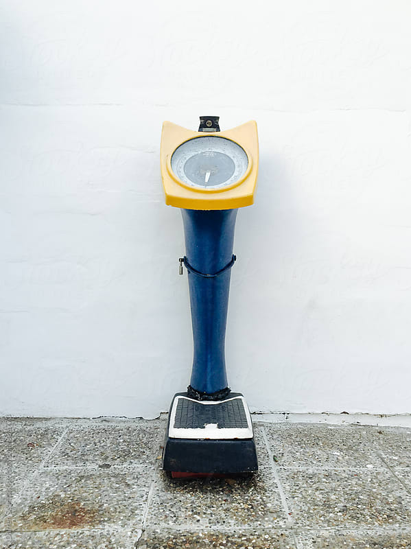 Weighing device outside against a wall by Darren Seamark for Stocksy United