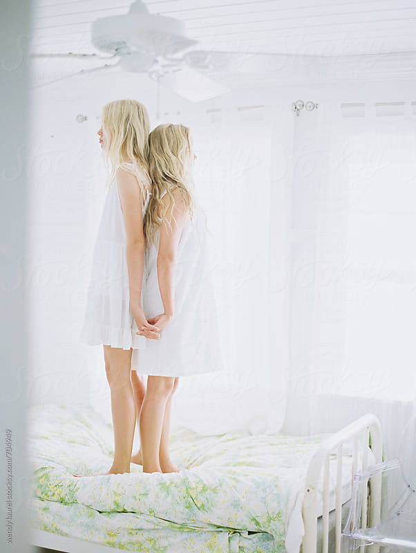 two girls standing back to back in white bedroom with floral sheet by wendy laurel for Stocksy United