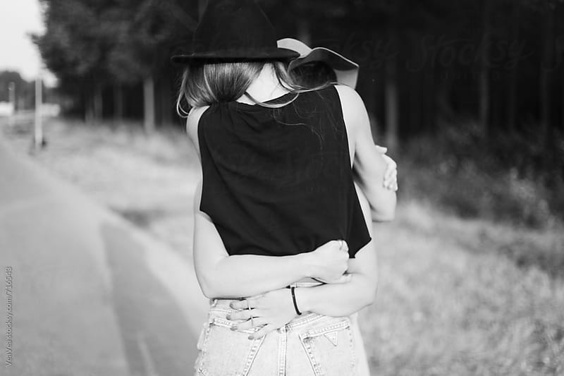 Two female friends hugging. From behind, black and white. by Marija Mandic for Stocksy United