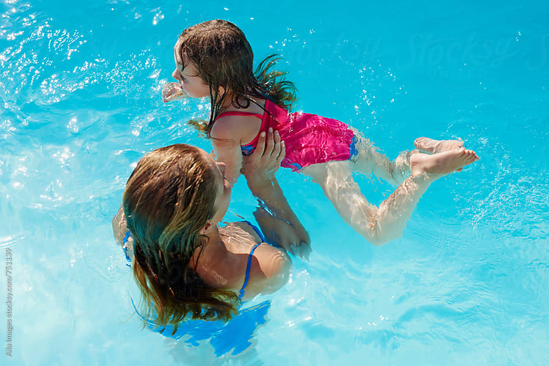 Mom and daughter having fun in pool learning to swim by Aila Images for Stocksy United