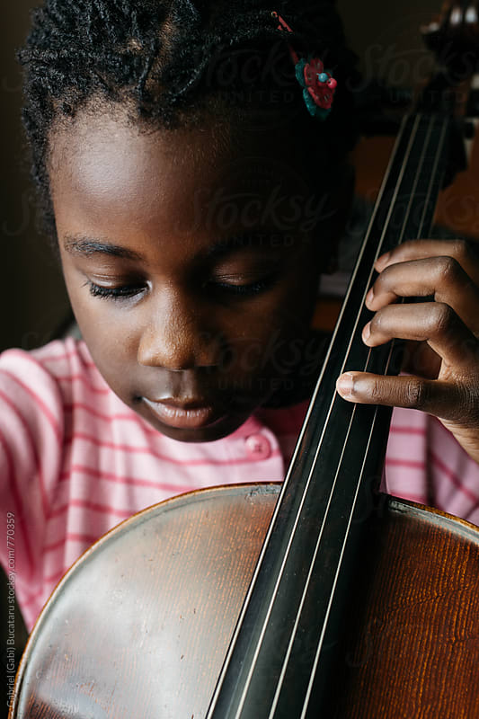 Black girl practicing cello by Gabriel (Gabi) Bucataru for Stocksy United