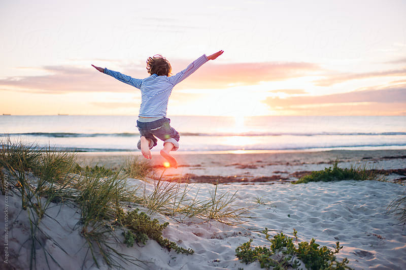 Boy jumping at the beach at sunset by Angela Lumsden for Stocksy United
