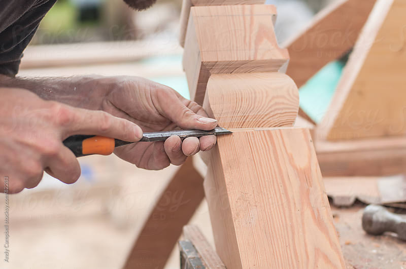 A carpenter carves wood with a chisel by Andy Campbell for Stocksy United