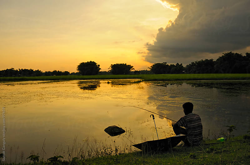 Man fishing at sunset by Saptak Ganguly for Stocksy United