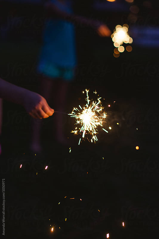 Children holding sparklers at dusk by Amanda Worrall for Stocksy United