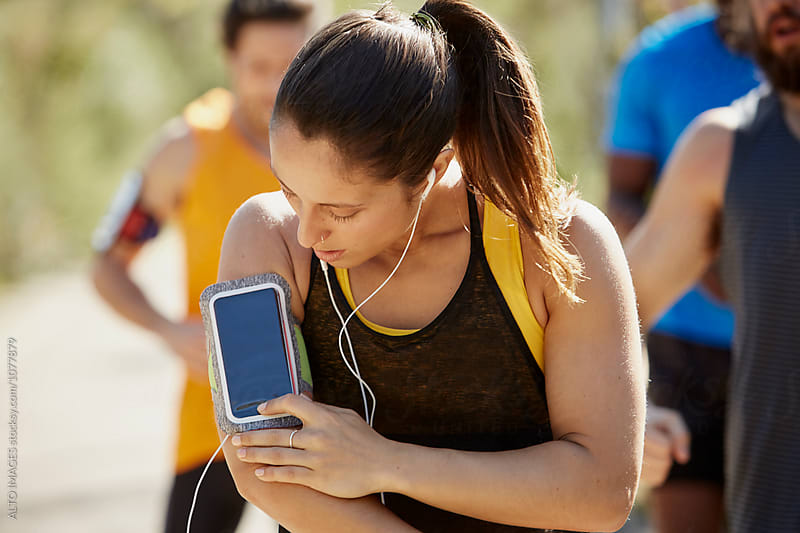 Female Athlete Listening To Music Through Smartphone by ALTO IMAGES for Stocksy United