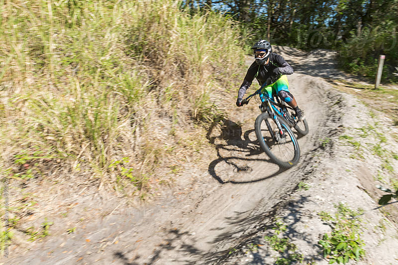 Mountain biker riding on a dirt trail by Adam Nixon for Stocksy United