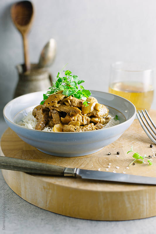 Stroganoff with rice and a glass of wine. by Darren Muir for Stocksy United