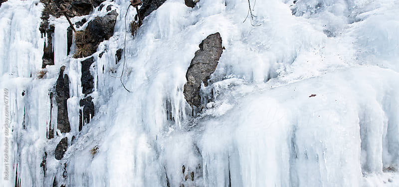 Big ice wall hanging on a mountain by Robert Kohlhuber for Stocksy United
