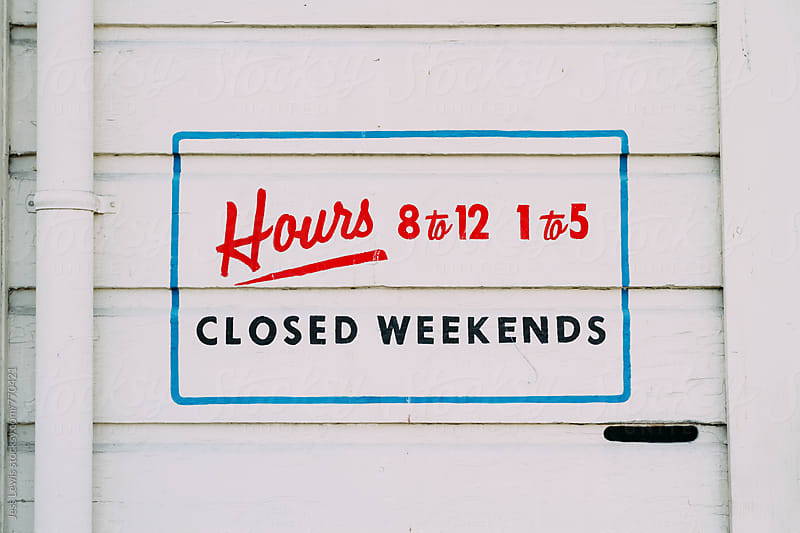 store hours painted on outside wall by Jess Lewis for Stocksy United
