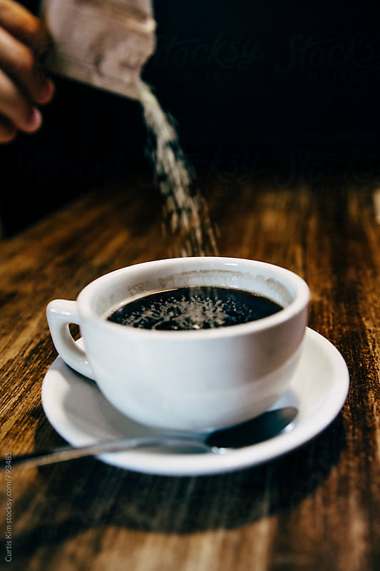 Pouring sugar into a cup of black coffee by Curtis Kim for Stocksy United