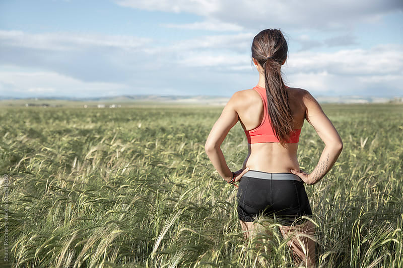 a young woman in workout clothes standing in a wheat field looking at the horizon by Shaun Robinson for Stocksy United