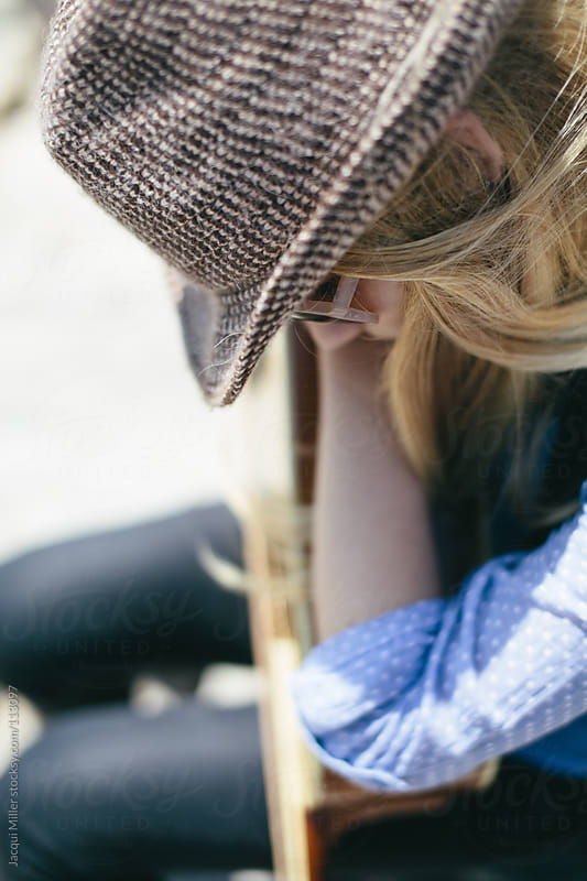 Girl wearing a wool hat rests on her guitar by Jacqui Miller for Stocksy United