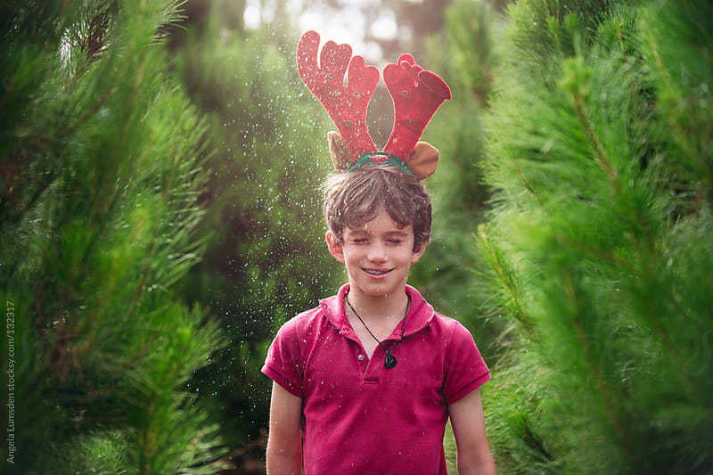 Boy with glitter amongst christmas trees by Angela Lumsden for Stocksy United