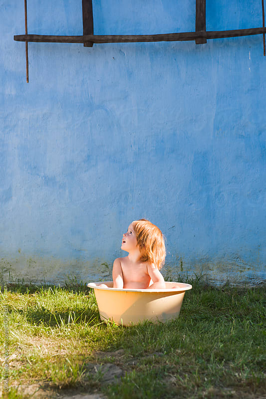 Toddler girl bathing in the backyard in a plastic basin by RG&B Images for Stocksy United