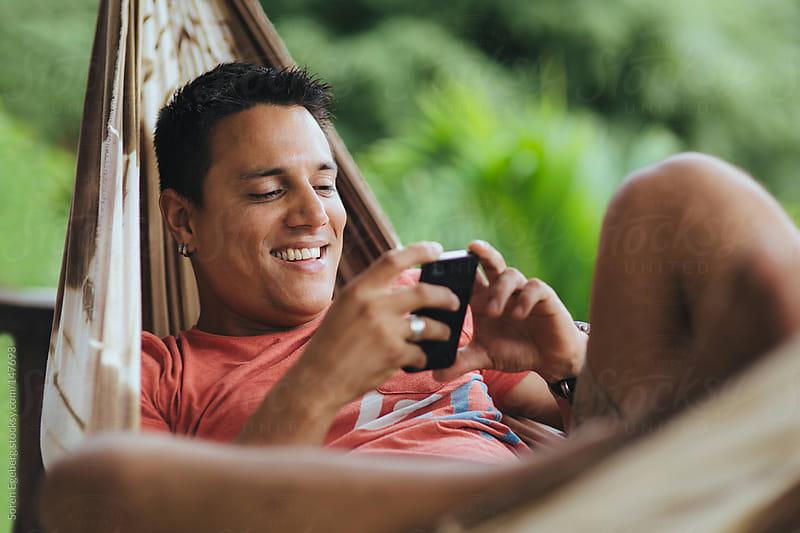 Smiling man lying in hammock using mobile smart phone for messaging. by Soren Egeberg for Stocksy United