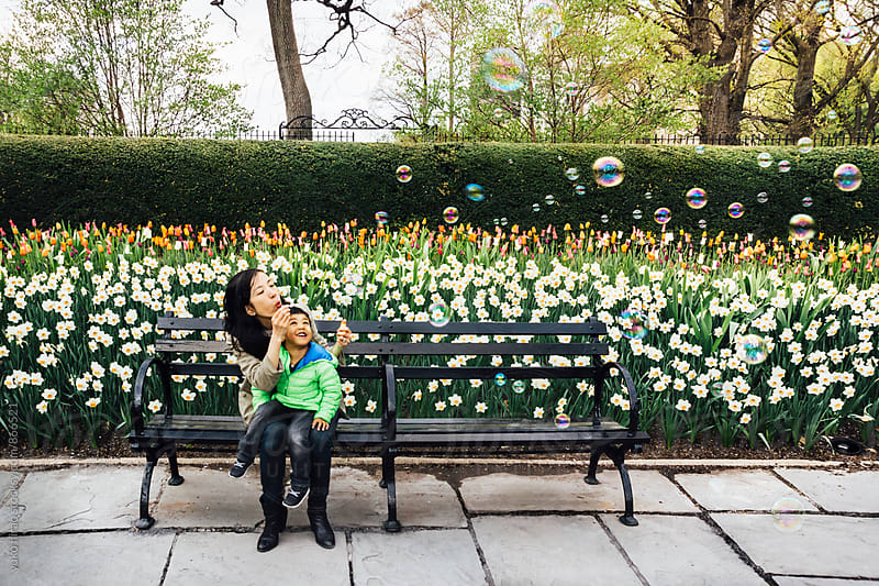 Asian mother and son, blowing bubbles in front of flowers by yuko hirao for Stocksy United