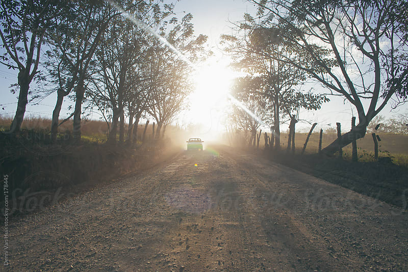 Car driving over dusty sandy dirt road.  by Denni Van Huis for Stocksy United
