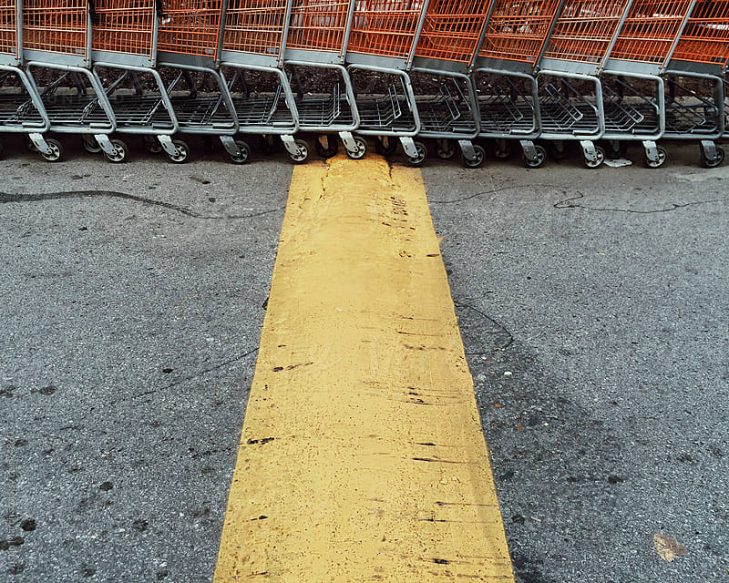 Orange shopping carts in a line by Justin March for Stocksy United