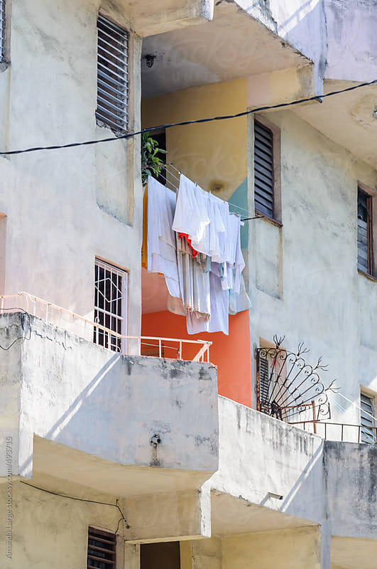 Laundry hanging outside an apartment window in Havana, Cuba. by Amanda Large for Stocksy United