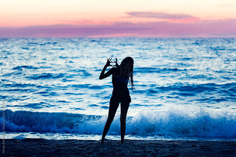 Young Woman Makes a Heart Gesture at Twilight on the Beach  by Helen Sotiriadis for Stocksy United