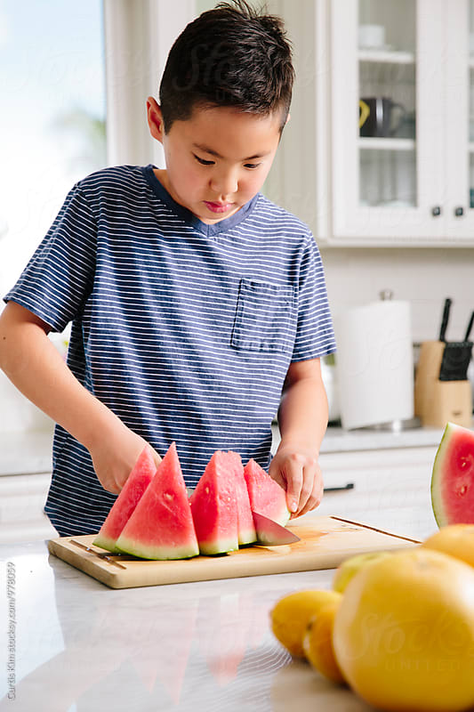Asian boy slicing up watermelon by Curtis Kim for Stocksy United