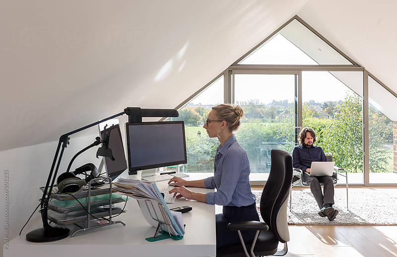 Couple running their business from their home office. by Paul Phillips for Stocksy United