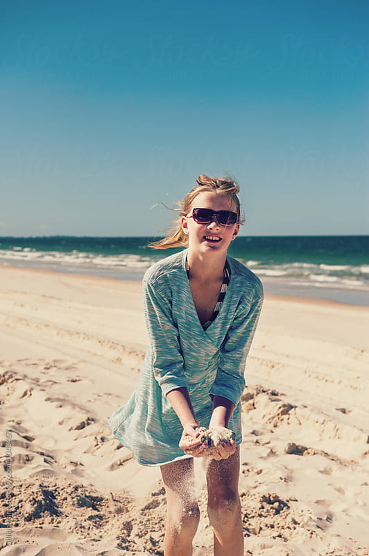 tween girl playing in the sand at the beach, wearing sunglasses by Gillian Vann for Stocksy United